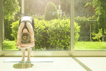 Attractive fit young yogi woman wearing sportswear practicing forward fold uttanasana at home. Female stretching at yoga center class, full length windows, garden view w bushes. Background, copy space
