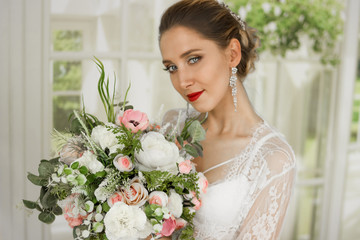 Portrait of a girl in a white lace with a bouquet. White robe, negligee. With a hairdress bun.