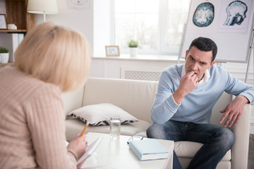 Interesting advice. Doubtful reflective man sitting during therapy while biting nails