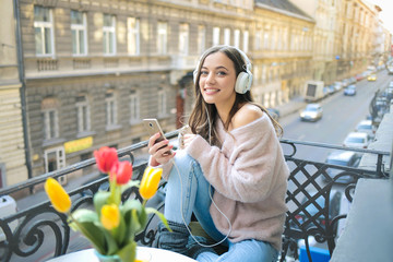 Cute girl having good time on her balcony, listening music and checking her phone