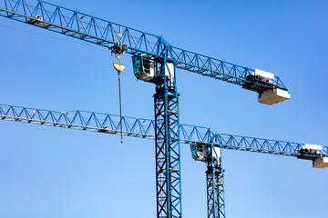 Tower crane on a construction site against a blue sky