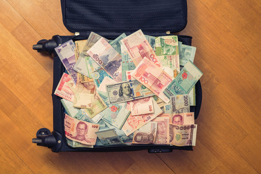 Suitcase full money of south-east Asia with American hundred dollar bill. Currency of Hong Kong, Indonesia, Malaysia, Thai, Singapore dollar.