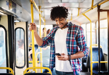 Young cheerful handsome man is enjoying the music during his ride and holding onto the bar while standing in a bus.