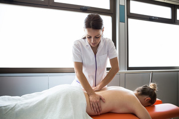 Attractive young woman in medical overall kneading back of faceless female patient.