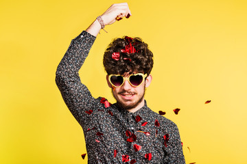 Studio portrait of a young man in love with sunglasses on a yellow background.