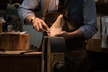Shoemaker cutting  shoe mold out of wood with knife