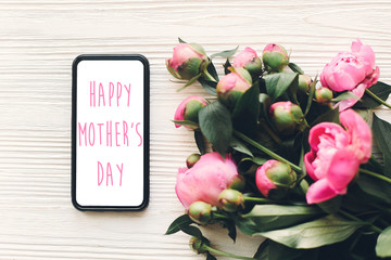 happy mother's day text on phone screen and pink peonies on rustic white wooden background in light. floral greeting card concept, flat lay. mothers day. tender spring image