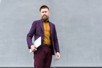 Stylish bearded businessman standing with laptop