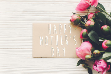 happy mother's day text on craft card and pink peonies bouquet on rustic white wooden background in light. floral greeting card concept, flat lay. mothers day. tender spring image