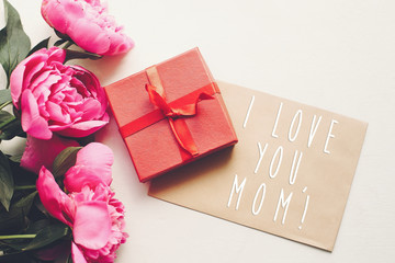 mom i love you text on craft card and pink peonies bouquet with gift box on rustic white wooden background in light. floral greeting card concept, flat lay. happy mother's day