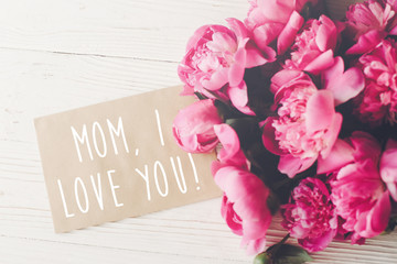 mom, i love you text on craft card and pink peonies bouquet on rustic white wooden background in light. floral greeting card concept, flat lay. happy mother's day . tender image