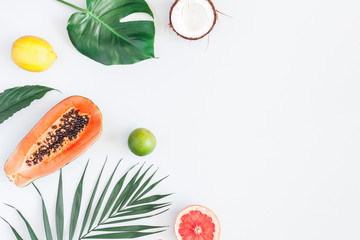 Summer tropical composition. Green palm leaves and tropical fruits on gray background. Summer concept. Flat lay, top view, copy space