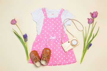 Baby girl spring outfit, pink dress, shoes, wooden camera toy and pink tulips, top view