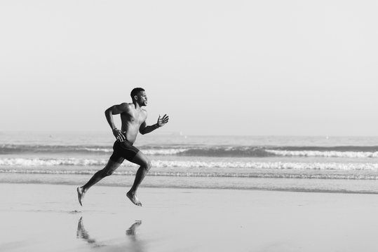 Black man running barefoot by the sea on the beach. Powerful runner sprinting and training on summer.