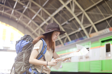 Young Asian woman is looking at map and enjoy traveling at the train station.