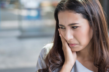 woman with toothache; portrait of woman suffering from toothache pain, tooth decay, tooth sensitivity; girl oral health care, dental care concept; asian young adult woman model