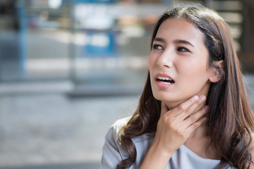 sick woman with sore throat; portrait of woman suffering from cold, flu, sickness with sore throat inflammation; woman health care, body care, sickness, pain concept; asian young adult woman model