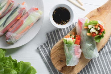 Asian fresh spring rolls. Raw cucumber, carrot, lettuce, bell pepper, tofu cheese inside rice paper. Top view.