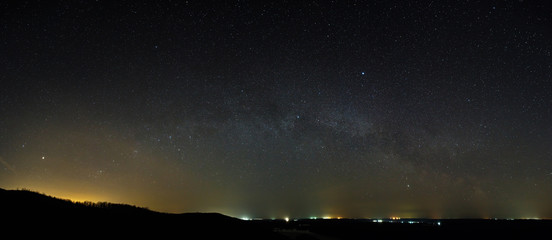 Stars of the Milky Way galaxy in the night sky above the skyline. Panoramic view of the starry space.