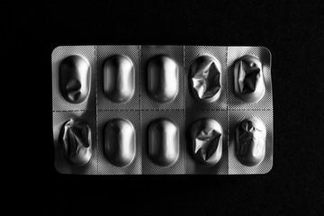Used medicine foil packaging on black