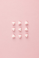 Triangular pills ordered in rows on pink background