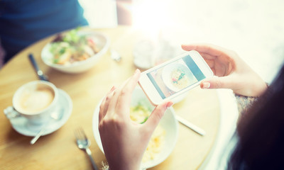 people, technology, eating and dating concept - close up of couple with smartphones picturing food at cafe or restaurant