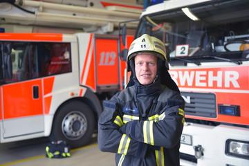 Beruf Feuerwehrmann - Portrait in der Feuerwache vor Feuerwehrfahrzeugen im Depot - Rettungsdienst 112 // firemen in the fire station in front of fire engines in the depot - rescue service