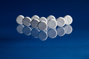 Rows of white prescription tablets on a blue background
