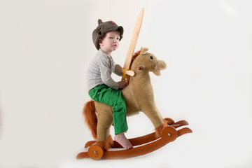 Funny child in old military cap with red star, on toy horse-rocking horse with wooden sword. Boy dreams of battles, victories and adventures. Concept training of spirit, education morale, patriotizm