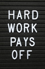 The phrase Hard Work Pays Off in white plastic letters on a letter board as a concept for effort determining success