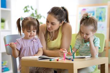 kindergarten female teacher helping kids in artclass