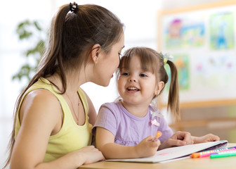 Mother whispering her child daughter while she draws a picture in nursery
