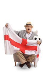 Excited elderly soccer fan sitting in an armchair and holding an English flag