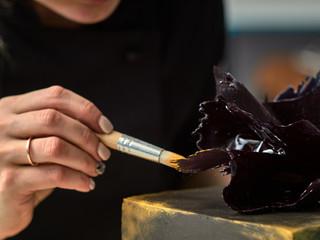 Step-by-step preparation of black designer cake. The confectioner decorates a black cake, gold food paint.
