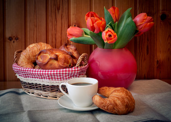 Cup of coffee, pastry and tulip  flowers. Selective focus.