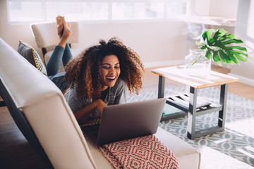 Smiling woman using a laptop while lying on the sofa