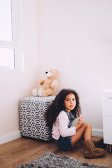 african girl sits next to her teddy bear at home