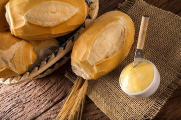 "Basket of ""French bread"", traditional Brazilian bread with butter on wood background."