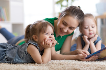Children laughing and having fun reading stories with their mother laying on floor at home