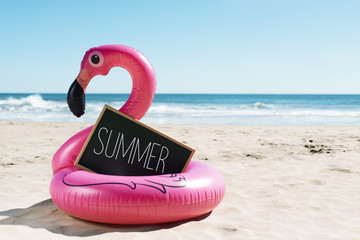 Tuinposter Flamingo flamingo swim ring on the beach and text summer