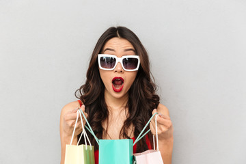 Shocked brunette woman in casual clothes and sunglasses opening packages