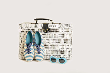 White wicker suitcase on a white background. Women's accessories - a hat, sunglasses and striped blue sneakers.