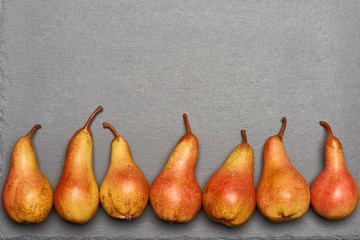 Top view of ripe yellow orange pears lying in line on gray slate background with blank copy space above