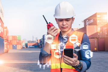 The abstract image of the engineer looking to the hologram from his smartphone in the port. the concept of engineering, shipping, shipyard, business, transportations and internet of things.
