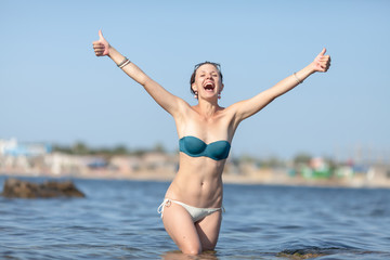 Girl standing in sea water, shows thumbs up and shouts