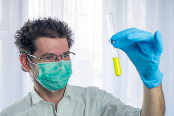 weird looking doctor holds yellow liquid test tube in his hand, concept dangerous medicine. selective focus