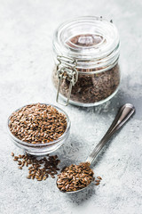 Flax seeds in glass jar, bowl and spoon on concrete background. Selective focus, space for text.