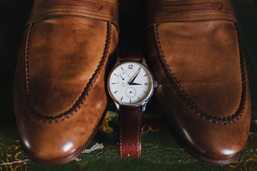 The wrist watch is next to the men's leather shoes