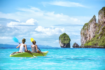 Two girls kayaking kanoeing beautiful sea bay