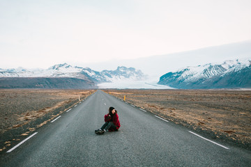 Young hipster woman sitting on the road in countryside on background of beautiful mountains. She is in warm clothes. Windy weather.